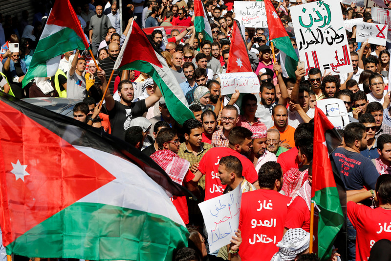 Crowd of dozens carry Jordanian flags, banners