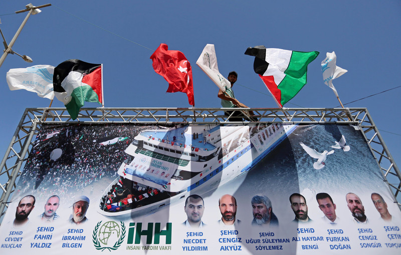 Large banner with flags, photos and names of victims