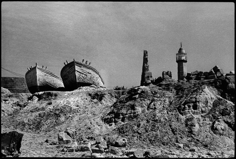 Two boats on a desolate hilltop with a minaret in the background