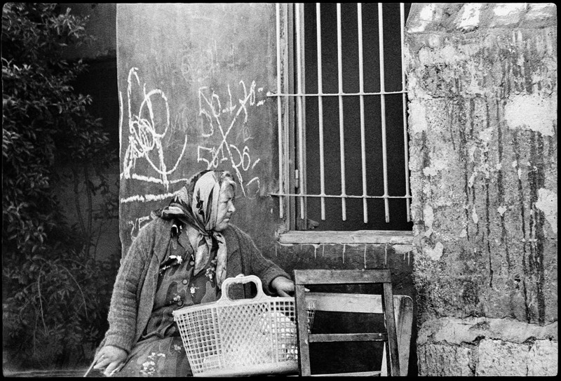 Woman with basket on her lap sits in front of building with a barred window