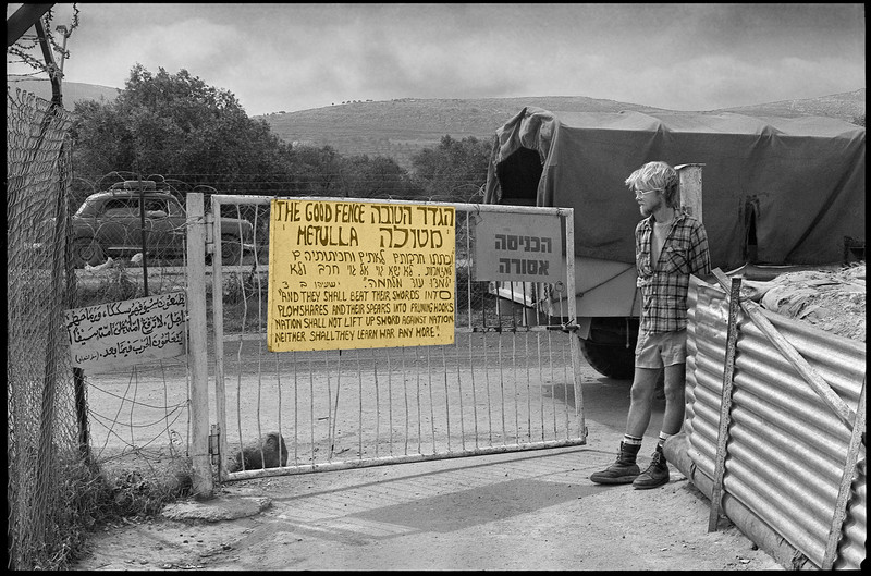 Young man stands in front of gate with sign reading The Good Fence