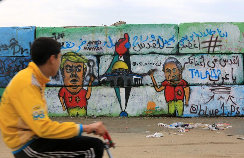 A boy looks at graffiti on a wal