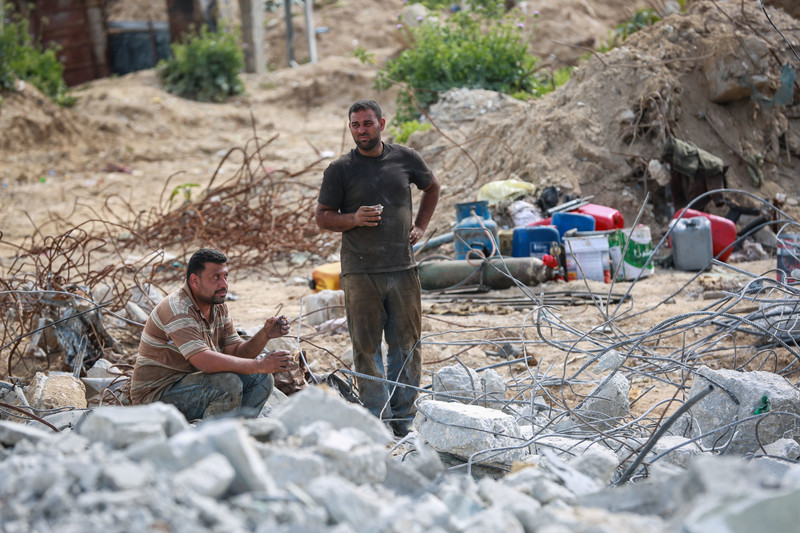 Two men enjoy a break in the middle of some rubble, both holding plastic cups of coffee