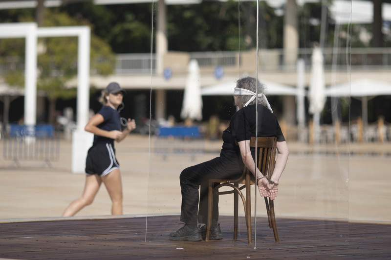Blindfolded woman cuffed to a chair sits in a glass box