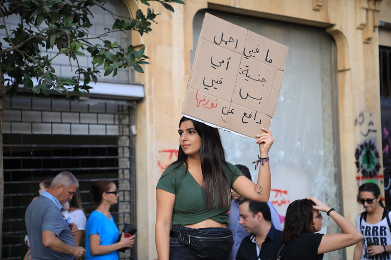 A woman holds up a sign with Arabic writing on it.