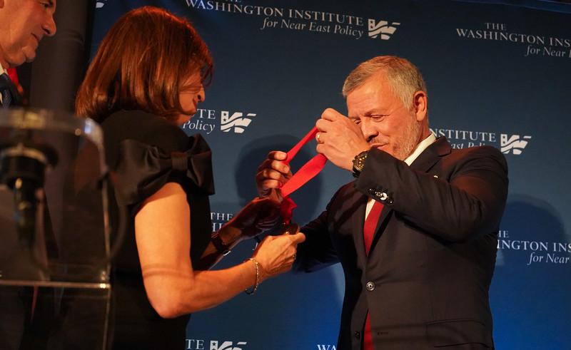 Woman gives man medal
