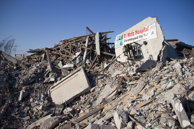 Banner on rubble says Al Wafa Hospital Destroyed by Israel