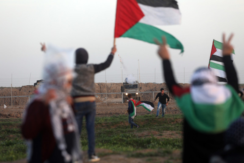 Palestinians hold flags at boundary fence with Israeli army jeep on opposite side
