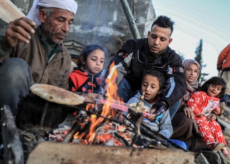 Three adults and three children warm bread around an open fire.