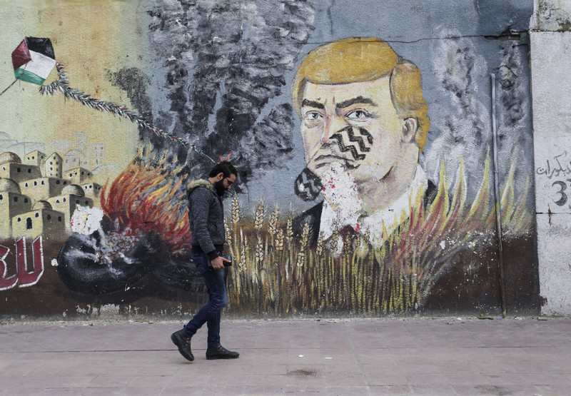 A man walks past a mural depicting US president Donald Trump with a footprint across his face