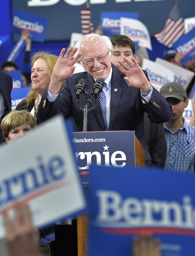Smiling man raises arms