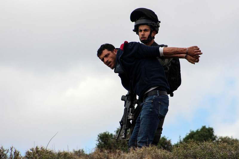 A soldier restrains a man who is in handcuffs