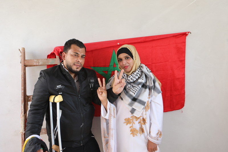 A couple flash the victory sign in front of a Moroccan flag.