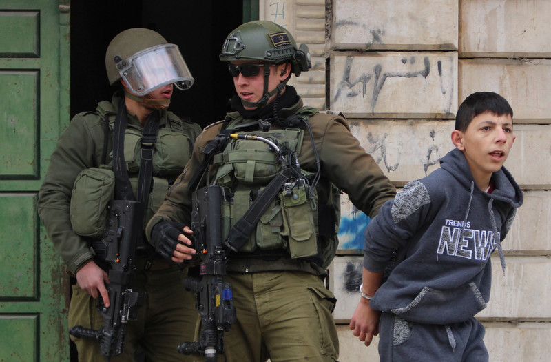Two full armed soldiers holding handcuffed boy