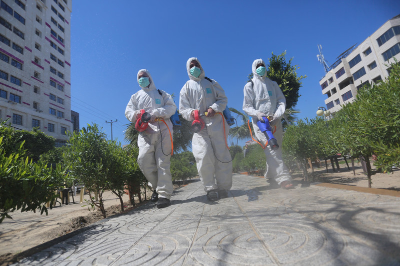 Three workers in uniform disinfect street