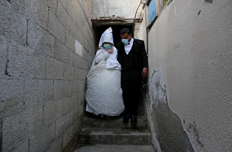 Woman in wedding dress and man in suit stand on steps