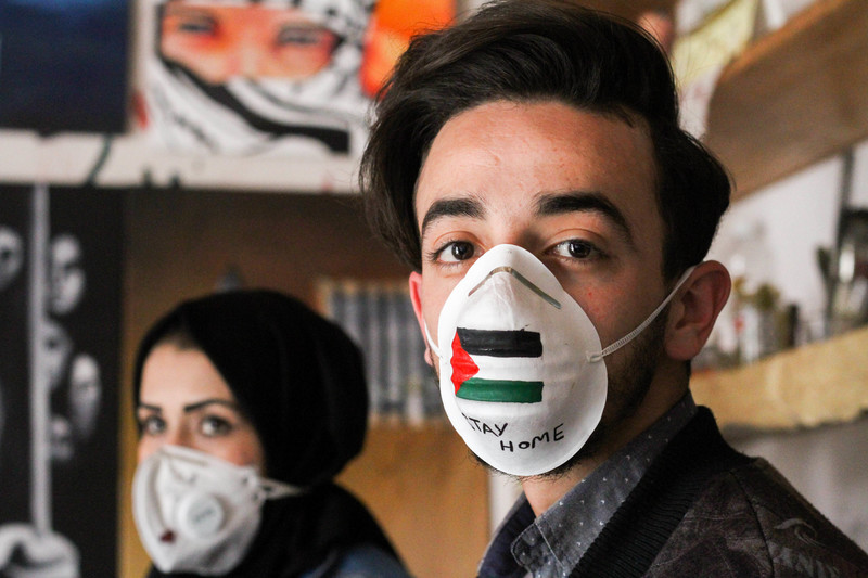 "A man and a woman wear painted face masks, one bearing the Palestinian flag and the words: ""Stay at home""."