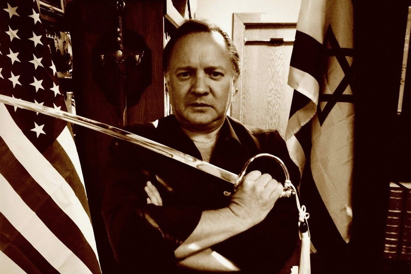 Man with sword flanked by US and Israeli flags