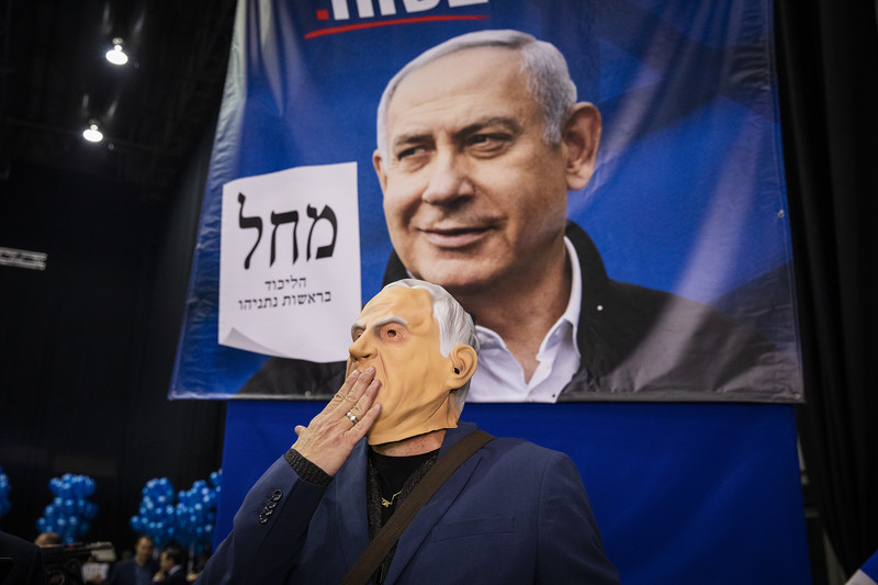a person wearing a mask stands before an election poster