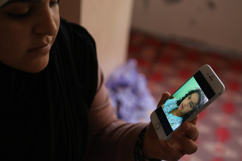 A woman holds a phone showing a picture of herself as a young girl