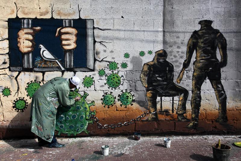Man spray painting graffiti on a wall