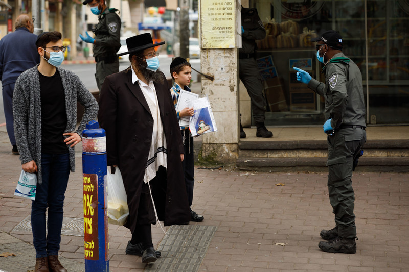 An Israeli policeman in a face mask gestures at two men, also in face masks, and one boy without