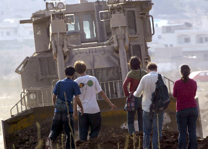 A group of people is dwarfed by a massive armored bulldozer