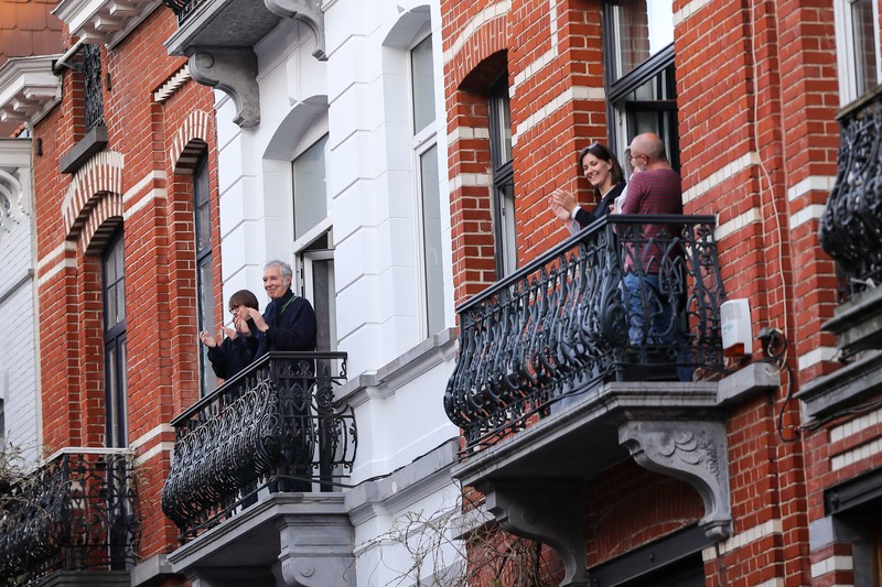 Smiling people clap on adjacent balconies