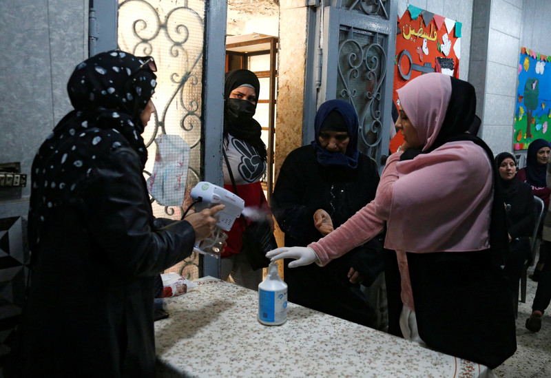A woman sprays another woman's hands as two women look on