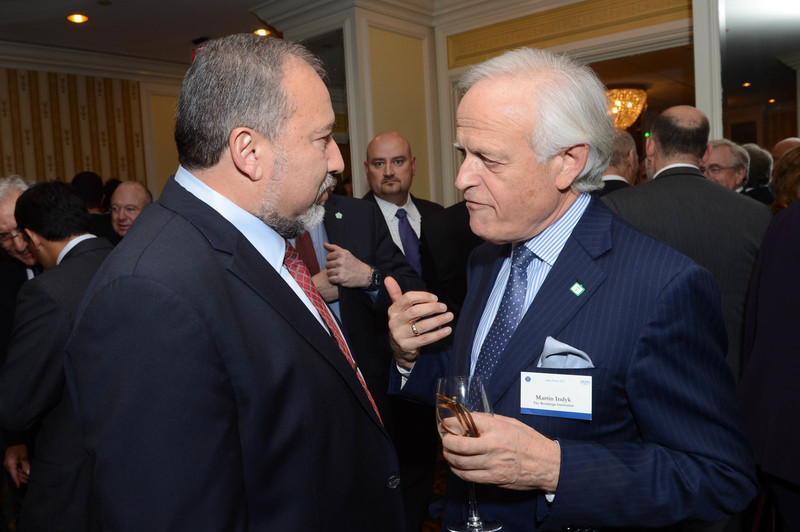 Two men talk together at conference with people in background