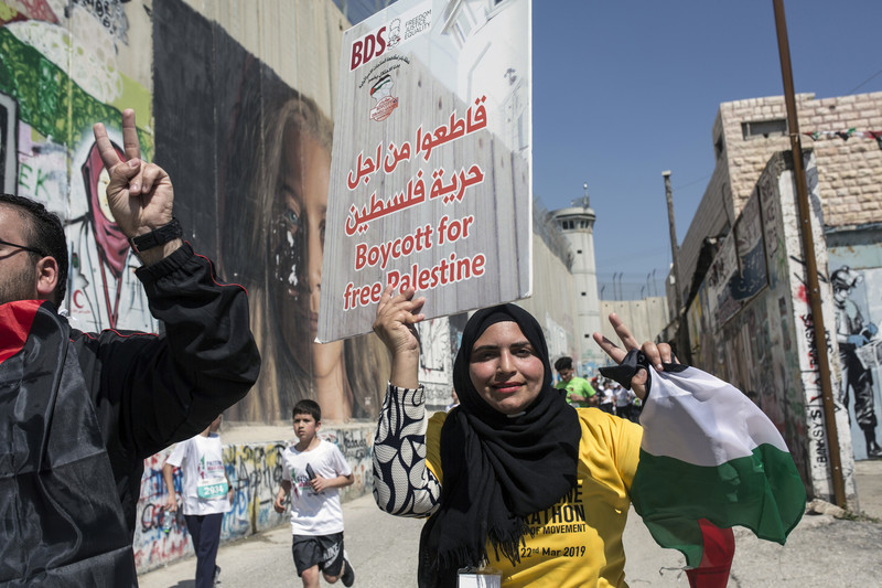 A woman makes a victory sign while holding a poster