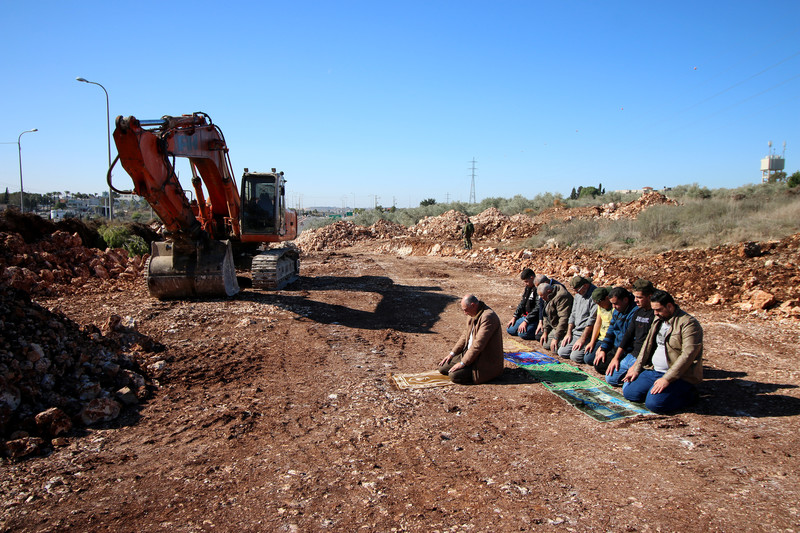 Men pray near construction equipment