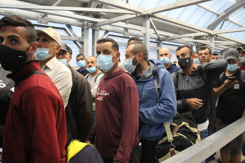 Men wearing surgical masks in queue