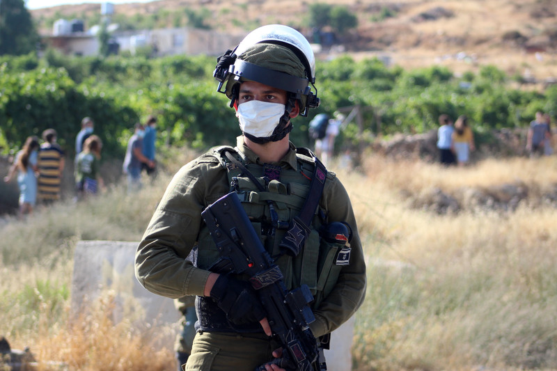 Heavily armed soldier wearing protective mask