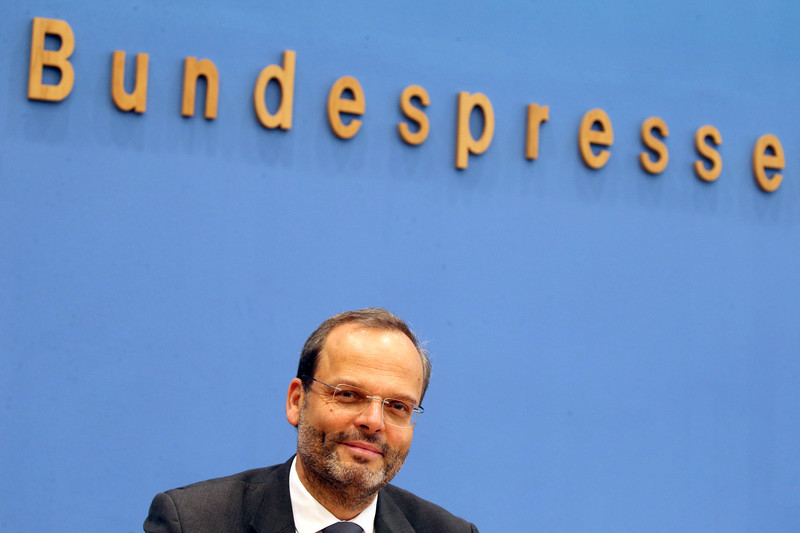 Smiling man sits a press podium