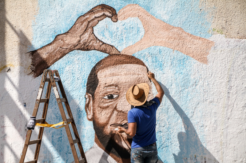A man paints a mural on a wall in Gaza