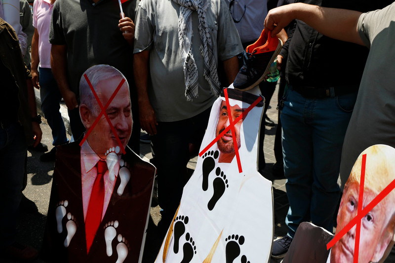 People hold images of regional leaders with foot marks on them