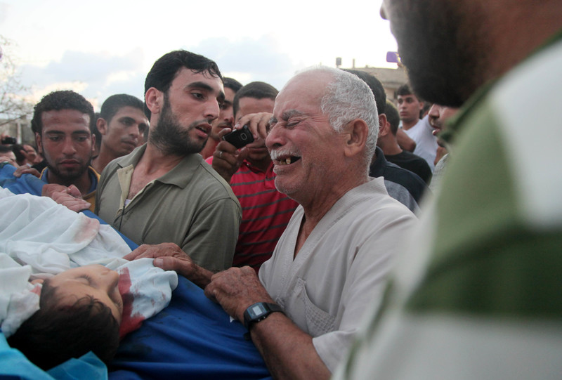 Man cries over body of child as others look on