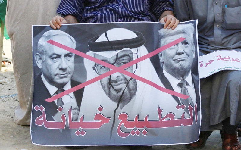 Man holds banner with three men on it