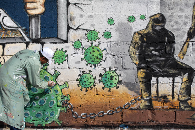 Man paints wall with images representing the virus and prisoners