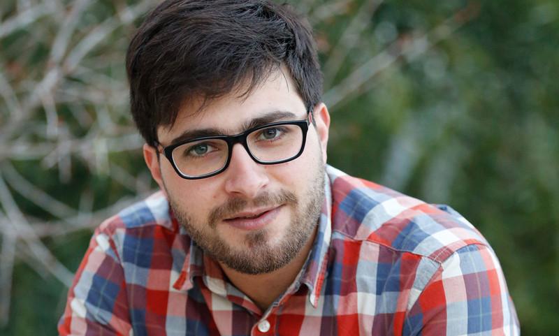 Headshot of smiling man wearing glasses