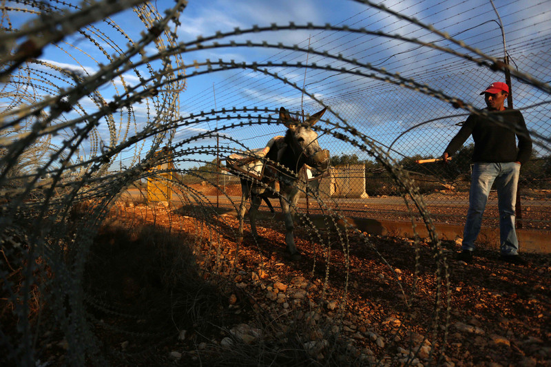A man and his donkey is seen through barbed wire