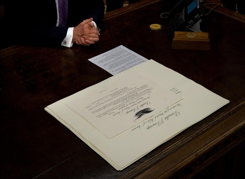 A document lies on a wooden desk