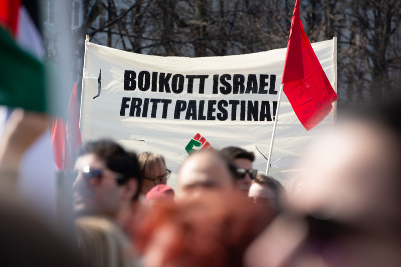 Crowd stands in banner calling for boycott of Israel and freedom for Palestine