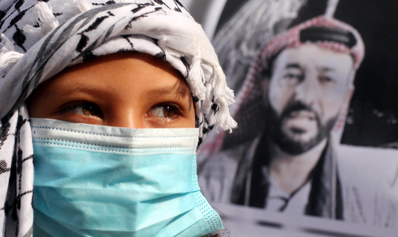 Child wearing protective mask near poster of a man
