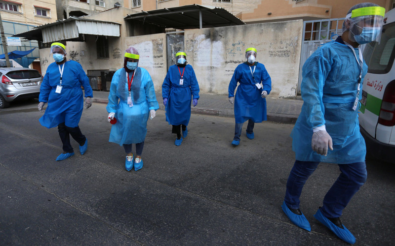 Five nurses in protective gear and masks walk down a street