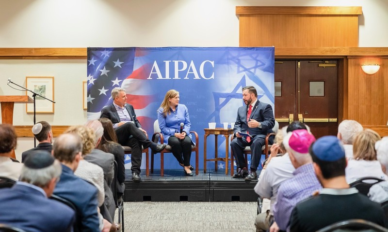 Woman and two men sit on podium with AIPAC sign