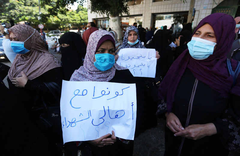 Women in face masks carry posters during a protest