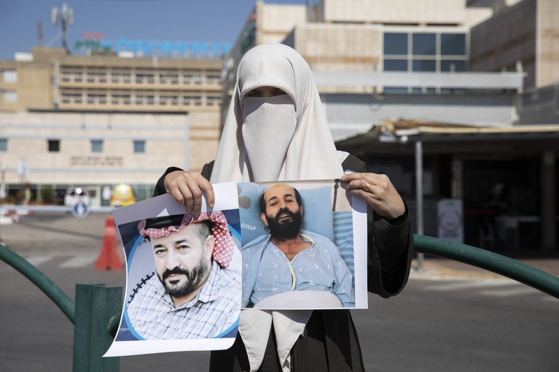Woman wearing a veil holds two portraits of a man
