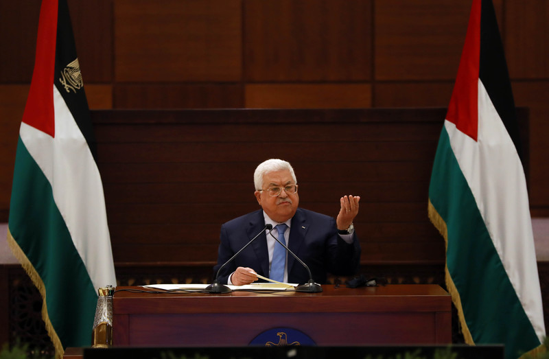 Mahmoud Abbas gestures while seated between two Palestinian flags